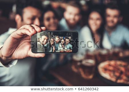 Stock photo: Young happy friends sitting in cafe while drinking alcohol.