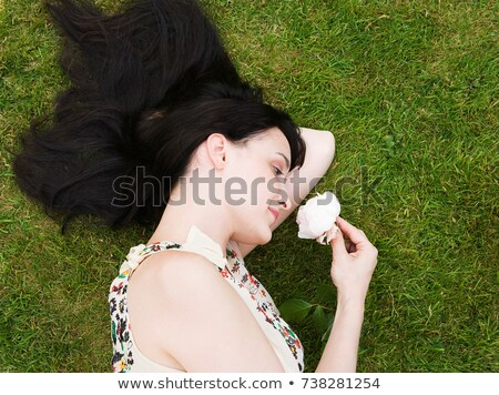 Woman laying on grass, smelling a rose Stock photo © IS2