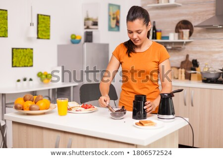 Woman in kitchen grinding coffee beans Stock photo © IS2