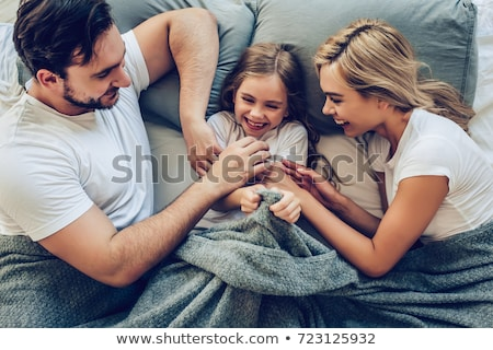 Parents having fun together with their daughter. stock photo © deandrobot
