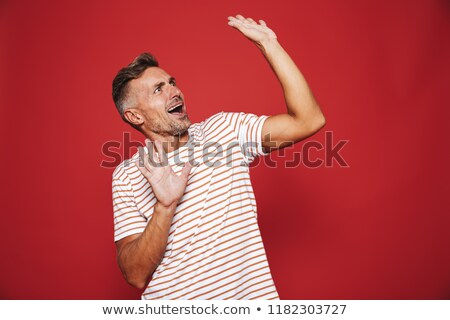 Excited man in striped t-shirt rejoicing and looking aside at co Stock photo © deandrobot