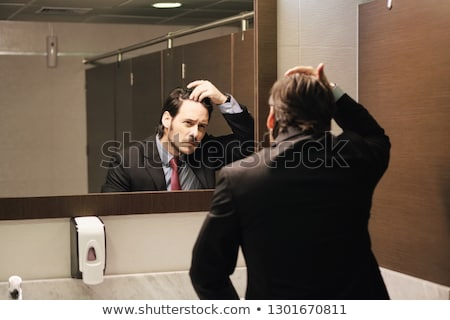 worried hispanic business man looking at hairline in office restrooms stock photo © diego_cervo