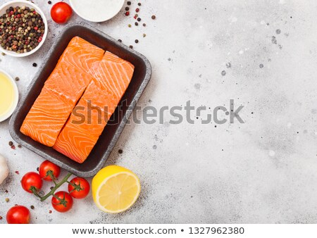 Plastic container with fresh salmon slice with oil tomatoes and lemon on stone kitchen background. W Stock photo © DenisMArt