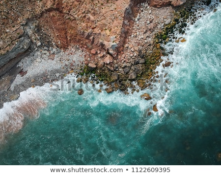 Aerial top view to a stone beach of seashore, turquoise water and crashing foam waves. Top view from Stock photo © artjazz