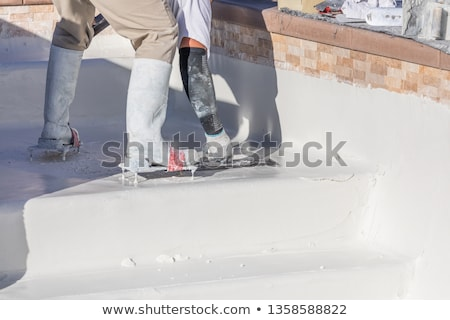 Worker Wearing Spiked Shoes Smoothing Wet Pool Plaster With Trow Stock photo © feverpitch