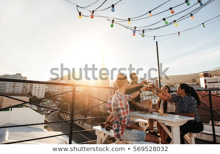 happy friends toasting drinks at rooftop party stock photo © dolgachov
