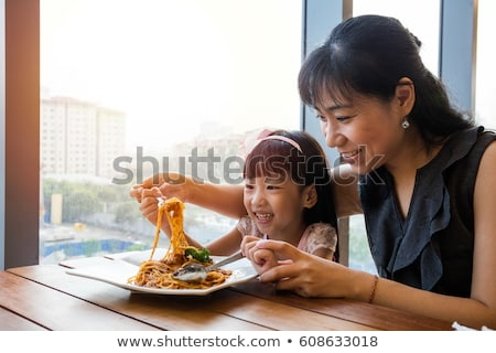 Foto d'archivio: Happy Mother And Daughter Eating Spaghetti Bolognese In The Rest