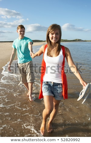 Romantic Young Couple Walking Along Shoreline Of Beach Holding H Stock photo © monkey_business