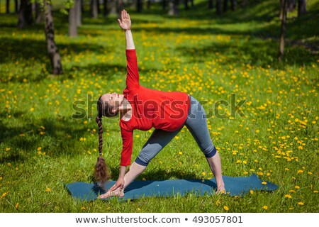 Doing extended triangle pose on grass Stock photo © pressmaster
