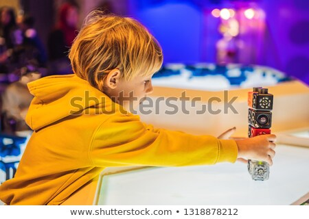 The boy plays with the electronic designer on the light table VERTICAL FORMAT for Instagram mobile s stock photo © galitskaya