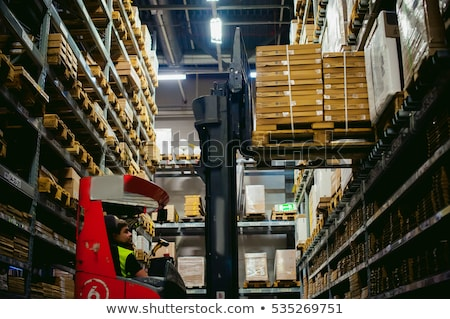 Worker driving a forklift in logistics delivery center Stock photo © Kzenon