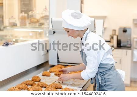 Confectioner woman baking pastry roles and chocolate bread Stock photo © Kzenon