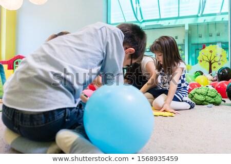 Group of children surrounding their teacher during educational activity Stock photo © Kzenon