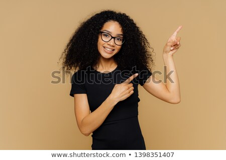 Delighted pleased dark skinned female points at upper right corner, shows place for your advertising Stock photo © vkstudio
