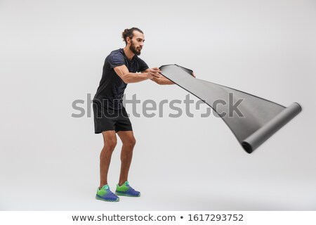 Image of young sportsman in tracksuit holding yoga mat while doi Stock photo © deandrobot