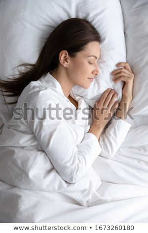 Woman indoors at home lies in bed sleeping under blanket. Stock photo © deandrobot