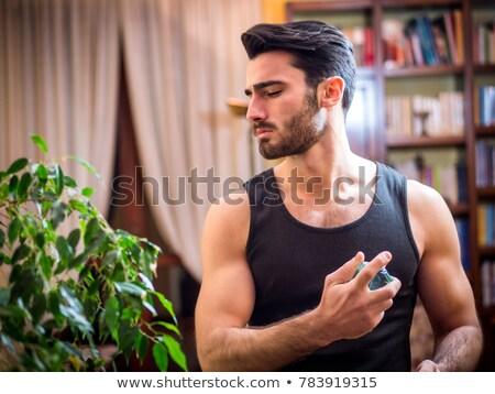 Foto stock: Man Spraying Perfume Cologne To His Neck