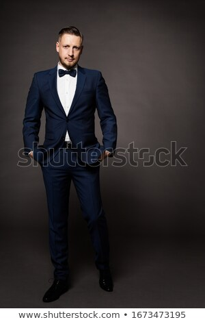 man posing in studio wearing tuxedo with hands in pockets Stock photo © feedough