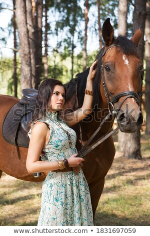 Smiling woman cowgirl walking with horse on farm Stock photo © deandrobot