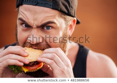 Angry irritated young man eating hamburger outdoors Stock photo © deandrobot