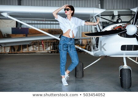 Smiling gorgeous young woman standing near small plane Stock photo © deandrobot