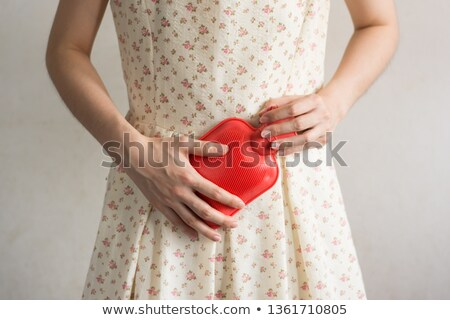 Young Woman Holding Hot Water Bag On Stomach Stock photo © AndreyPopov