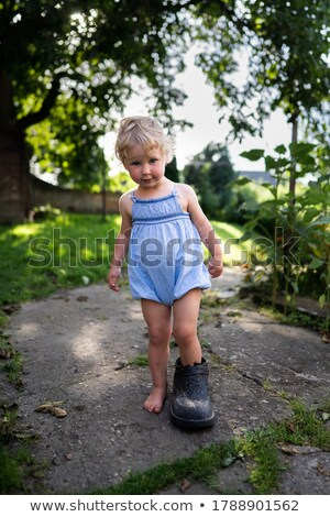 smiling little girl with big shoes stock photo © julenochek