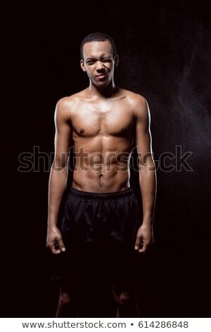 African american muscular man blinking and posing on black  Stock photo © LightFieldStudios
