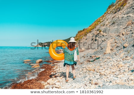 Beautiful young woman on wild rocky beach. Stock photo © artfotodima