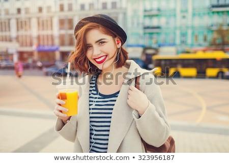 Mooie jonge dame hoofdtelefoon drinken sap Stockfoto © deandrobot