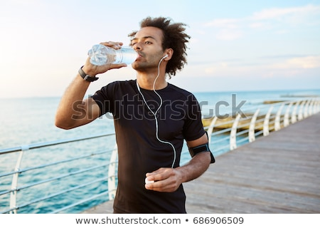 man drinking from water bottle during sports stock photo © kzenon