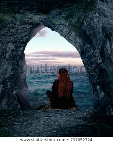 Adventurer admiring beautiful sunsets from mountain caves Stock photo © lovleah