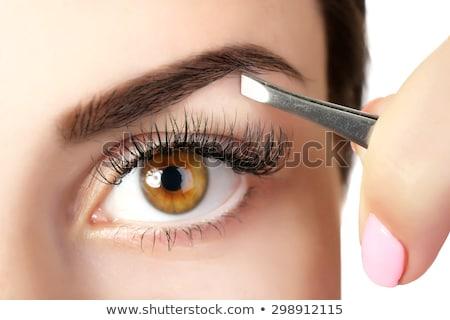 Beautician plucking eyebrows with tweezers of a woman Stock photo © Kzenon