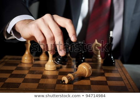 businessman playing chess game figures on wooden table for analy stock photo © snowing