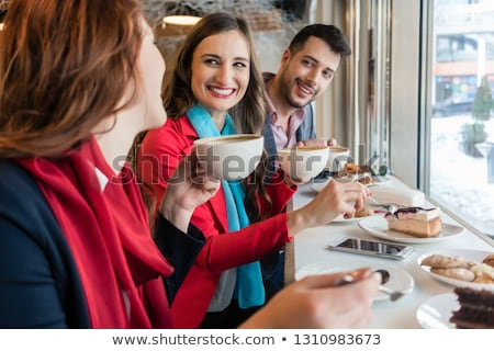 colleagues smiling while eating delicious cakes during break in a coffee shop stock photo © kzenon