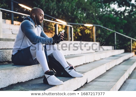 Sportsman outdoors using mobile phone. Stock photo © deandrobot