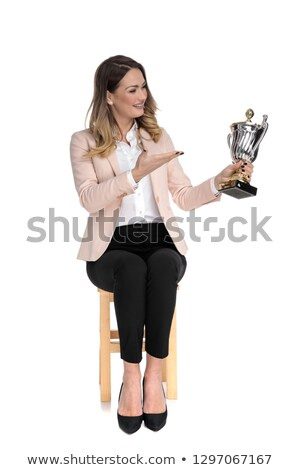 Stockfoto: Seated Businesswoman Presents Cup And Looks To Side
