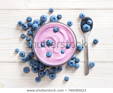 Fresh hommemade creamy blueberry yoghurt with fresh blueberries and silver spoon on stone kitchen ta Stock photo © DenisMArt