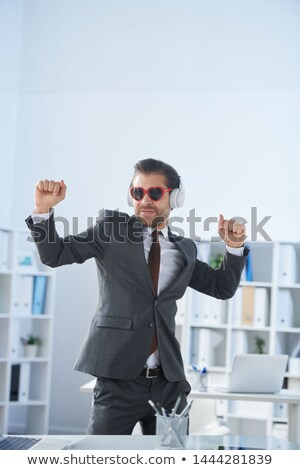 Happy man in formalwear, sunglasses and headphones dancing by workplace Stock photo © pressmaster