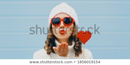 close up of hand holding red heart shaped lollipop stock photo © dolgachov