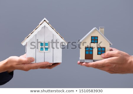 Close-up Of Couple's Hand Holding Different Miniature Houses Stock photo © AndreyPopov