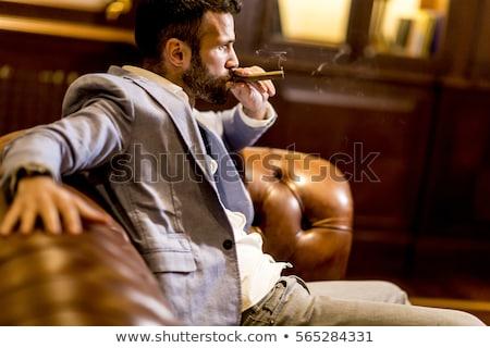 Bell'uomo seduta pelle divano fumare sigaro Foto d'archivio © boggy
