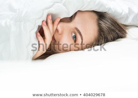 Kép meglepődött fiatal nő rejtőzködik pléd ágy Stock fotó © deandrobot