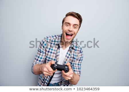 Portrait of excited man screaming and playing video game on cellphone Stock photo © deandrobot