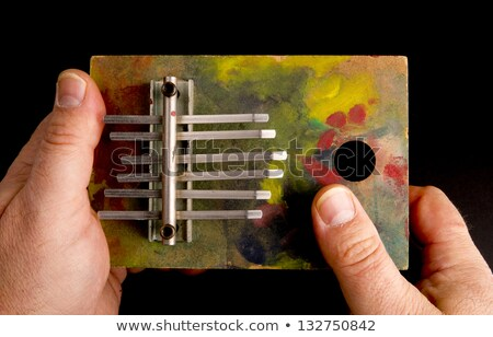 hands playing tune on musical instrument of the thumb harp stock photo © cboswell