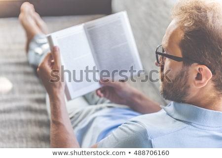 Férfi szemüveg olvas könyv kanapé jóképű férfi Stock fotó © feelphotoart