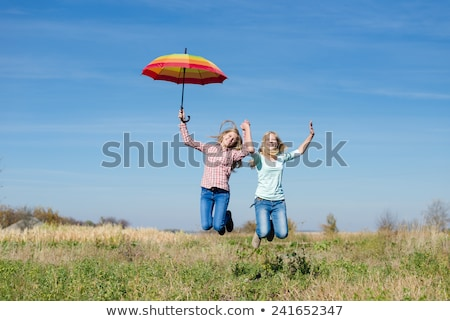 two blonde ladies having fun with colorful umbrellas stock photo © majdansky