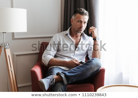 Handsome mature man using smartphone at home  Stock photo © deandrobot