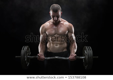 Muscular man holding barbell over black background Stock photo © deandrobot