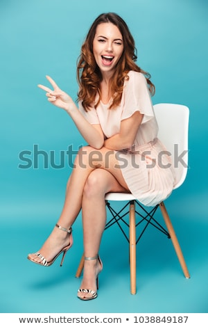portrait of a beautiful woman sitting on the chair and dressing gaiters stock photo © deandrobot